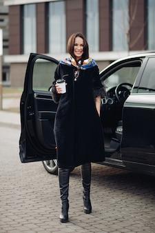 В полный рост модная дама в черном пальто и кожаных сапогах с ярким носовым платком на шее. она несет чашку кофе на вынос напротив открытой машины на улице.