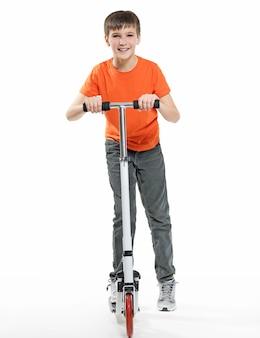 Полная длина счастливого ребенка, катающегося на скутере, изолированном на белом фоне