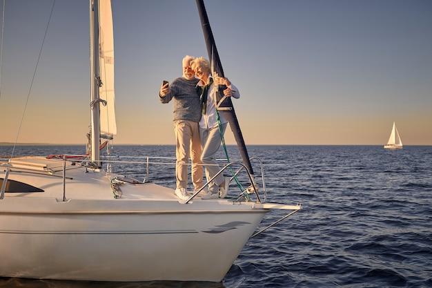 海に浮かぶ帆船の横に一緒に立っている幸せな年配のカップルの全長と