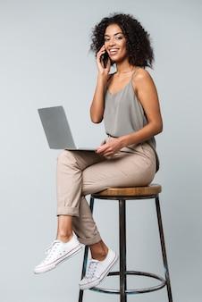 孤立した椅子に座って、ラップトップコンピューターで作業し、携帯電話で話しているカジュアルな服を着て幸せな若いアフリカの女性の全長