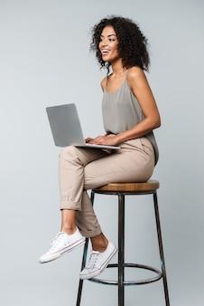 ラップトップコンピューターで作業し、孤立した椅子に座ってカジュアルな服を着て幸せな若いアフリカの女性の全長