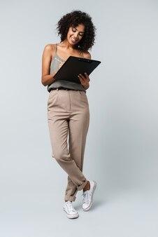 幸せな若いアフリカの女性の完全な長さは、メモ帳を持って、孤立して立って何気なく服を着て