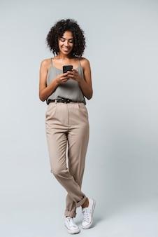 행복 한 젊은 아프리카 여자의 전체 길이 부담없이 격리, 휴대 전화를 들고 서 옷을 입고