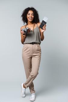 Полная длина счастливой молодой африканской женщины, небрежно одетой, стоя изолированно, держа фотоаппарат, показывая паспорт с билетами на самолет