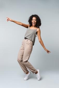 행복 한 젊은 아프리카 여자의 전체 길이는 부담없이 복사 공간을 가리키는 절연 서 옷을 입고