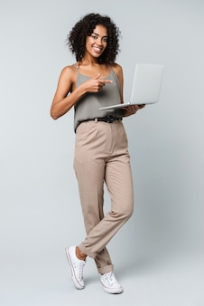ラップトップコンピューターで作業して、孤立して立って何気なく服を着て幸せな若いアフリカの女性の全長