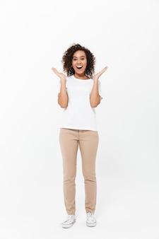 成功を祝って、白い壁に隔離されたカジュアルな服を着て幸せな若いアフリカの女性の全長