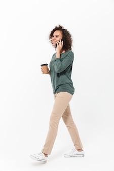 Полная длина счастливой молодой африканской женщины в повседневной одежде, изолированной над белой стеной, разговаривает по мобильному телефону, пьет кофе на вынос