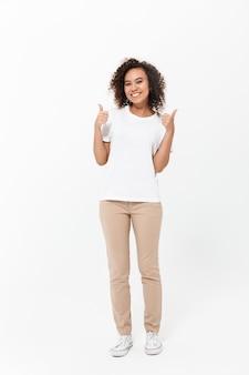 Полная длина счастливой молодой африканской женщины в повседневной одежде, изолированной над белой стеной, пальцы вверх