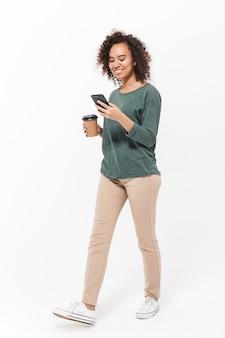 Полная длина счастливой молодой африканской женщины в повседневной одежде, изолированной над белой стеной, с помощью мобильного телефона, пьющей кофе на вынос