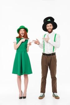 Счастливая молодая пара в костюмах празднует день святого патрика в полный рост, изолированные на белой стене, указывая пальцами друг на друга
