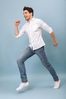 Полная длина счастливого молодого человека, повседневно одетого, прыгает, изолированного на синем