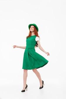 Полная длина счастливой молодой рыжеволосой девушки в зеленой шляпе, празднующей день святого патрика, изолированной над белой стеной, позирует
