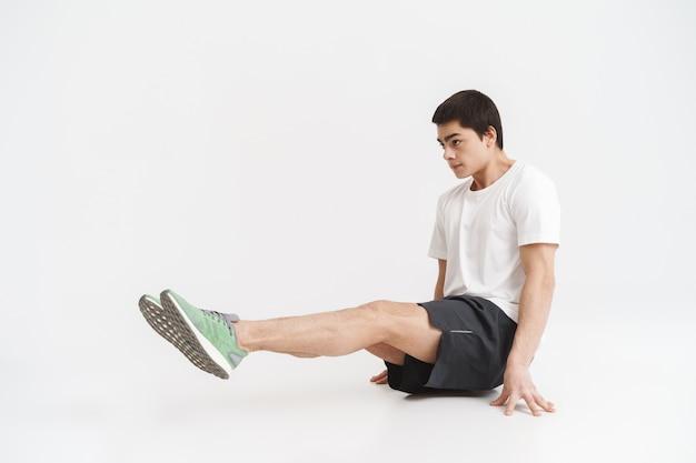 흰색 위에 핵심 운동을하는 건강한 운동가의 전체 길이