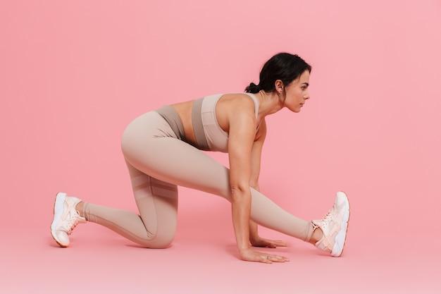 분홍색 벽에 격리된 스트레칭 운동을 하는 운동복을 입은 건강한 젊은 여성의 전체 길이