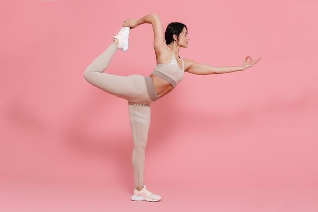 ピンクの壁に隔離されたストレッチ運動をしているスポーツウェアを身に着けている健康的なフィットの若い女性の全長