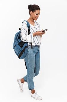 携帯電話を使用して、白い壁の上に孤立して立っているバックパックを運ぶ魅力的な若いアフリカの女性の肖像画の全長