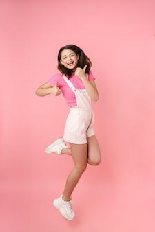 В полный рост довольно возбужденная молодая девушка-подросток прыгает изолированно, радуется, показывает палец вверх