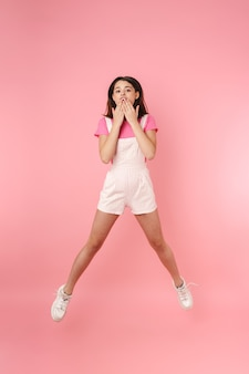 В полный рост довольно возбужденная молодая девушка-подросток прыгает изолированно, радуется