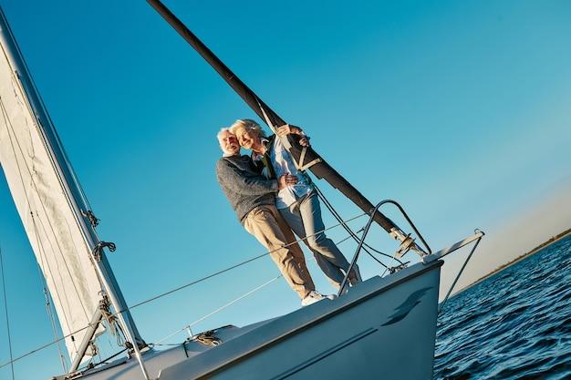 帆船やヨットのデッキの横に立っているロマンチックで幸せな年配のカップルの全長