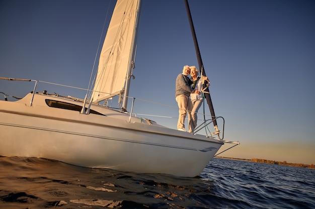 帆船の横に立っているロマンチックな引退したカップルの年配の男性と女性の全長または