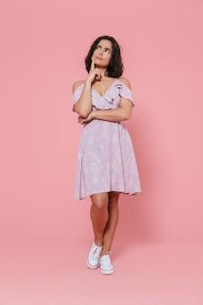 ピンクの壁の上に孤立して立っている夏のドレスを着て笑顔の若い女の子の全長