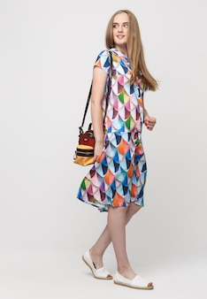 夏のドレスを着た若いエレガントな女の子の全長