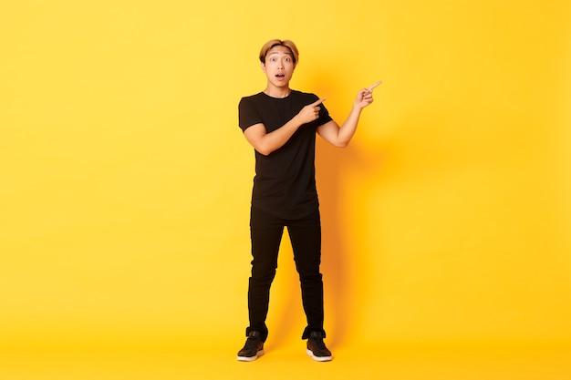 Изумленный и впечатленный привлекательный азиатский парень в полный рост, указывая пальцами в правом верхнем углу, показывает логотип, желтая стена