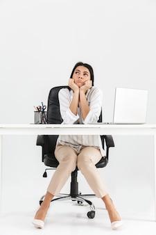 白い壁に隔離された机に座っている魅力的な退屈な若い実業家の全長