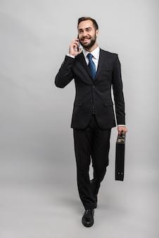 В полный рост привлекательный улыбающийся молодой бизнесмен в костюме, изолированный над серой стеной, несущий портфель, ходьба, разговор по мобильному телефону