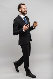 В полный рост привлекательный улыбающийся молодой бизнесмен в костюме, изолированном над серой стеной, в наушниках, используя мобильный телефон, попивая кофе на вынос
