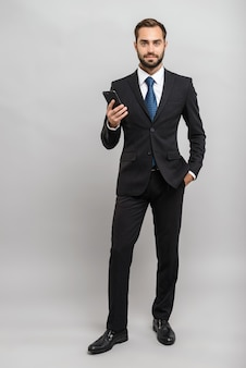 Полная длина привлекательного молодого бизнесмена в костюме, стоящего изолированно над серой стеной и держащего мобильный телефон