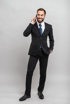 Полная длина привлекательного молодого бизнесмена в костюме, стоящего изолированно над серой стеной, разговаривает по мобильному телефону
