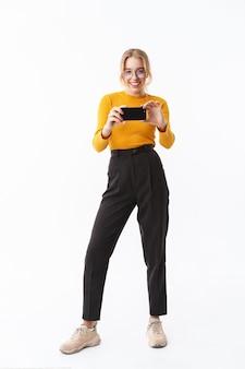 携帯電話で写真を撮る、白い壁の上に孤立して立っているセーターを着ている魅力的な若い女の子の全長