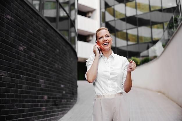 ビジネスセンターの外観で電話で話している魅力的な金髪のファッショナブルな実業家の全長。
