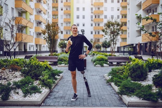建物に囲まれた公園に人工脚が立ってバナナを食べる魅力的な白人スポーツマンの全長。