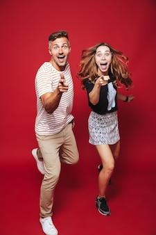 В полный рост привлекательные мужчина и женщина в полосатой футболке прыгают, показывая на вас указательные пальцы, изолированные на красном
