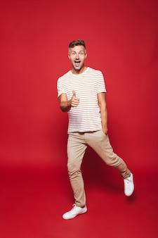 В полный рост привлекательный мужчина в полосатой футболке улыбается и показывает палец вверх изолирован на красном