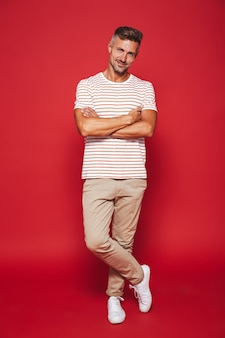 Полный рост привлекательный мужчина в полосатой футболке улыбается и стоит со скрещенными руками, изолированными на красном