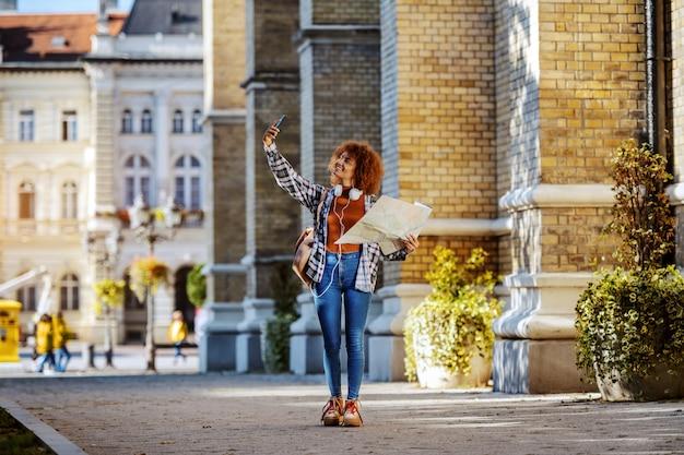 Во всю длину привлекательной молодой женщины смешанной гонки при вьющиеся волосы держа карту и принимая selfie пока стоящ outdoors городской. globetrotter.