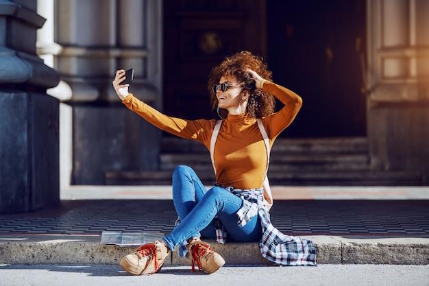 Во всю длину привлекательной молодой женщины смешанной гонки при вьющиеся волосы принимая selfie пока сидящ outdoors. рядом с ней карта. globetrotter.