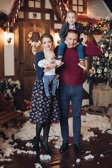 인공 눈으로 장식 된 방에 서있는 두 아들과 함께 매력적인 젊은 백인 가족의 전체 길이