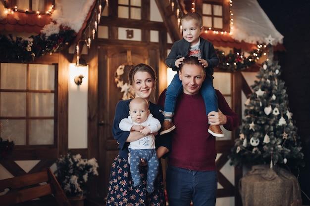 人工雪で飾られた部屋に立っている2人の息子を持つ魅力的な若い白人家族の全長