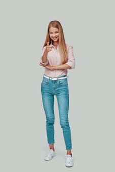Полная длина привлекательной молодой женщины, смотрящей в камеру и указывающей на вас, стоя на сером фоне