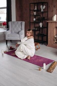 Полная длина красивой спокойной женщины в белом, обнимая себя, сидя на розовом коврике для йоги босиком и глядя вниз. комфортный деревянный интерьер.