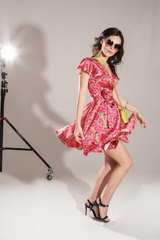 スタジオでカメラを見ながらバッグダンスとショートドレスの美しい女性のフルレングス。ファッション。ショッピング。夏のコンセプト