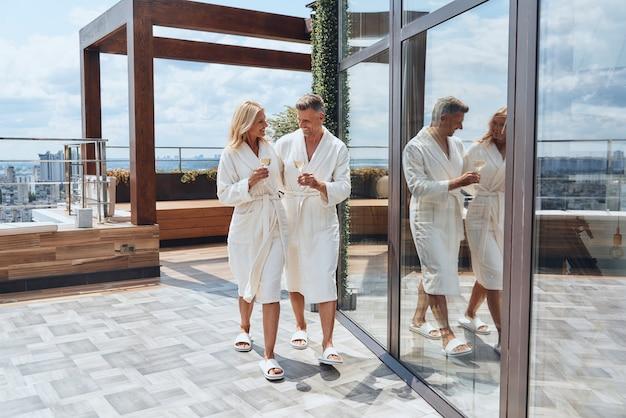고급 호텔에서 휴식을 취하면서 샴페인을 즐기는 목욕 가운에 아름 다운 성숙한 부부의 전체 길이...