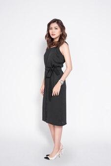 Полная длина красивой стильной азиатской женщины в элегантном повседневном черном наряде позирует