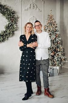 Полная длина красивой женщины обнимает ее муж в очках, позирует возле елки