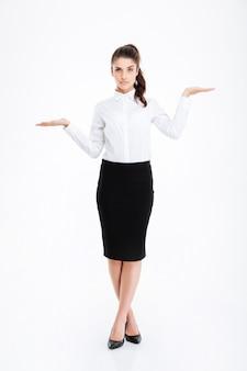 Полная длина красивой молодой бизнес-леди, стоящей и держащей copyspace на обеих ладонях над белой стеной